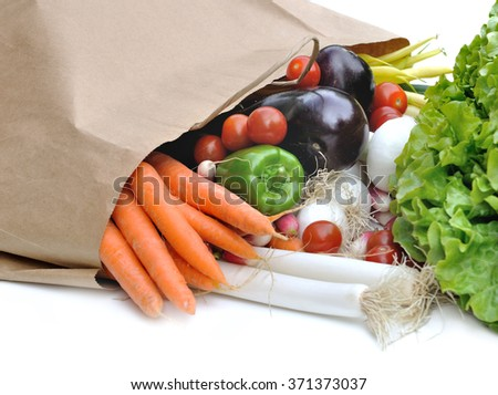 vegetables spilled a paper bag on white background
