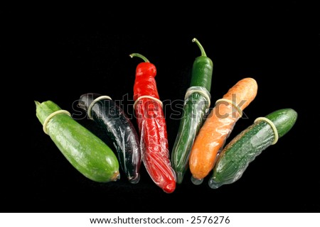 Vegetables with condoms on a black background - stock photo