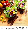 Vegetables with salad dish with spring edible flowers - stock photo
