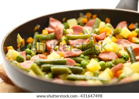 Vegetables with sausages fried in the pan