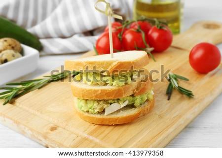 Vegetarian avocado sandwich on a wooden board. - stock photo