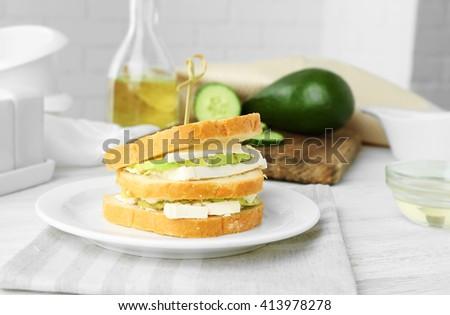 Vegetarian avocado sandwich on white plate. - stock photo