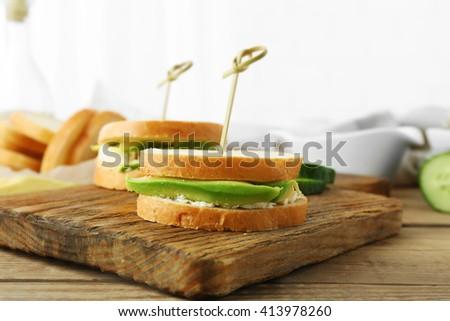 Vegetarian avocado sandwiches on a wooden board - stock photo