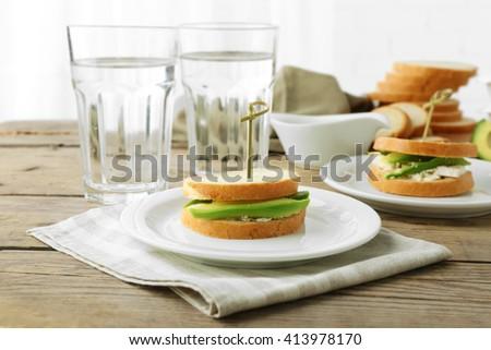 Vegetarian avocado sandwiches on white plate. - stock photo