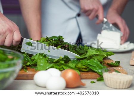 Vegetarian bakery concept. Chef's hands cutting feta cheese, spinach salad in kitchen of cafe, restaurant. Close up. Indoor shot