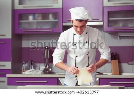 Vegetarian bakery concept. Smiling chef cook in uniform making slices of puff pastry, cooking french chausson. Indoor shot