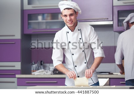 Vegetarian bakery concept. Smiling chef cook in uniform making slices of puff pastry, cooking french chausson. Indoor shot - stock photo