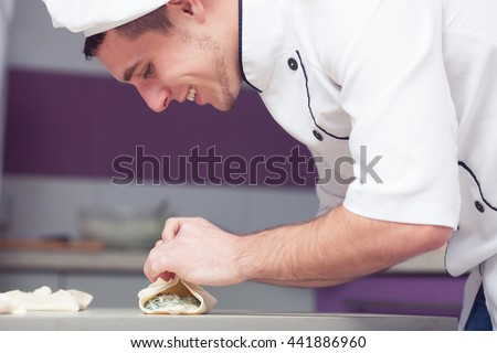 Vegetarian bakery concept. Smiling cook putting filler of spinach and soft feta cheese on slice of puff pastry and making french chausson. Close up. Indoor shot - stock photo