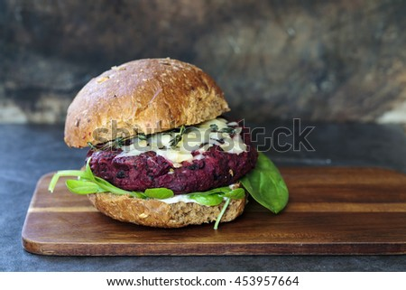 Vegetarian beetroot and black beans burger with melted cheese and thyme