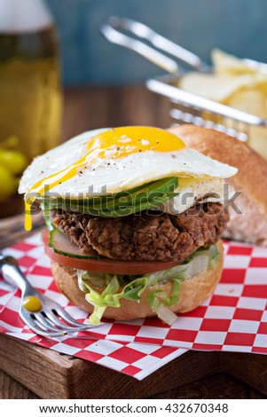 Vegetarian burger made with rice and beans with egg and avocado - stock photo