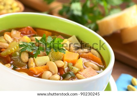 Vegetarian canary bean soup made of canary beans, celery, carrot, potato, tomato, leek, green onion with parsley on top (Selective Focus, Focus one third into the soup and the front of the parsley) - stock photo