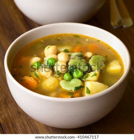 Vegetarian chickpea soup or stew with carrot, broad bean (fava bean), pea, potato, onion, garlic and parsley, photographed with natural light (Selective Focus, Focus in the middle of the first soup)
