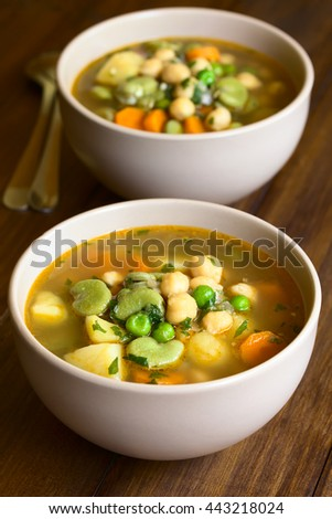 Vegetarian chickpea soup or stew with carrot, broad bean (fava bean), pea, potato, onion, garlic, parsley, photographed with natural light (Selective Focus, Focus in the middle of the first soup) - stock photo