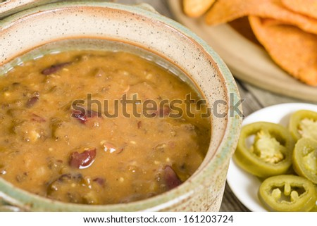 Vegetarian Chili - Chili made with soy protein and beans served with tortilla chips, pico de gallo, jalapenos, guacamole and sour cream. - stock photo
