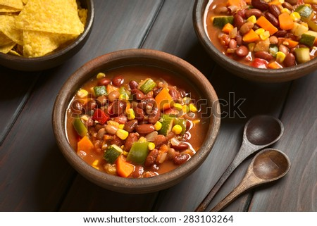 Vegetarian chili dish made of kidney bean, carrot, zucchini, bell pepper, sweet corn, tomato, onion, garlic, photographed with natural light (Selective Focus, Focus in the middle of the first dish)    - stock photo