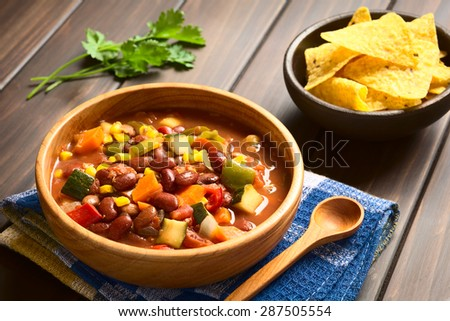 Vegetarian chili dish made of kidney bean, carrot, zucchini, bell pepper, sweet corn, tomato, onion, garlic, photographed with natural light (Selective Focus, Focus in the middle of the dish)    - stock photo