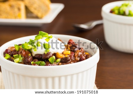 Vegetarian chili made with onions, tomatoes, corn, kidney and black beans, topped with sour cream and diced jalapeno, served with cornbread - stock photo