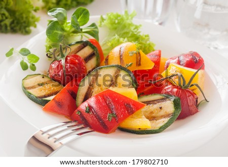 Vegetarian Close up of a serving of delicious roasted diced fresh vegetables in a white bowl garnished with fresh herbs and frilly lettuce with a mixture of colorful sweet bell peppers - stock photo
