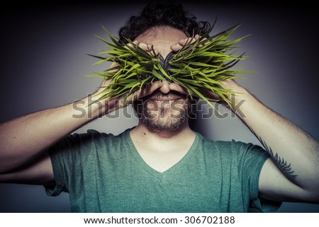 vegetarian concept, man with green grass in the mouth - stock photo