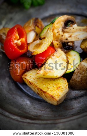 Vegetarian cooking. Organic roasted baked vegetables in vintage setting. Potatoes, paprika, mushrooms, onion, zucchini and herbs - stock photo