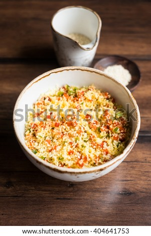 Vegetarian couscous warm salad made with red and green bell pepper with sesame seeds in a bowl, selective focus