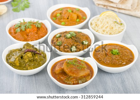 Vegetarian Curries - Selection of South Asian vegetarian curries in white bowls. Paneer Makhani, Palak Paneer, Aloo Matar, Baigan Bharta, Chilli Potatoes and Bhindi Masala, Pilau Rice and Chapattis.