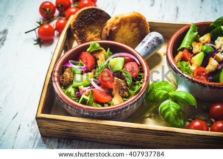 Vegetarian dish on a wooden table, a typical Tuscan dish, panzanella. - stock photo