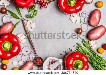 Vegetarian food background with various organic vegetables, wooden spoon and  seasoning for tasty cooking. Top view composing, frame.  Healthy eating and diet food concept.