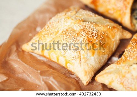 Vegetarian food concept. Baked chaussons with seeds of sesame on parchment paper in cafe. French cuisine. Close up. Indoor shot