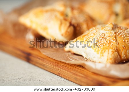 Vegetarian food concept. Baked chaussons with seeds of sesame on wooden board with parchment paper in cafe. French cuisine. Close up. Indoor shot - stock photo