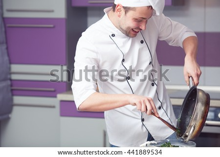 Vegetarian food concept. Smiling chef in white uniform cooking spinach in metal pot. Close up. Copy-space. Indoor shot - stock photo