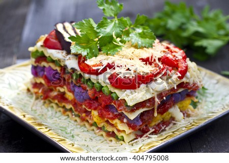 Vegetarian food: vegetable lasagna with mozzarella, parmesan green beans, purple cauliflower, grilled bell pepper and eggplant - stock photo