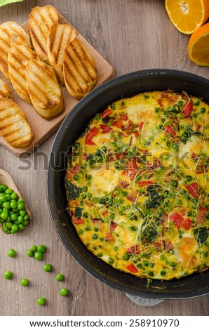 Vegetarian frittata with spinach, prosciutto and microgreens, fresh crispy baked baguette flavored with fresh pepper and olive oil - stock photo