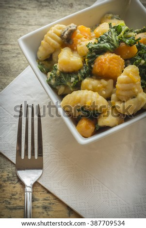Vegetarian gnocchi dish with squash kale and mushrooms