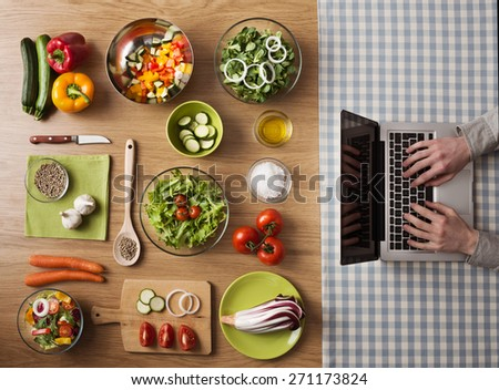 Vegetarian healthy food preparation at home on kitchen table with hands typing on a laptop on the right, top view - stock photo