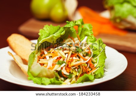 Vegetarian kitchen & healthy food concept. Fresh vegetable salad of celeriac, carrot, apple, iceberg lettuce and pignolia (pine) nut. Ingredients on wooden cutting board. Close up. Indoor shot - stock photo