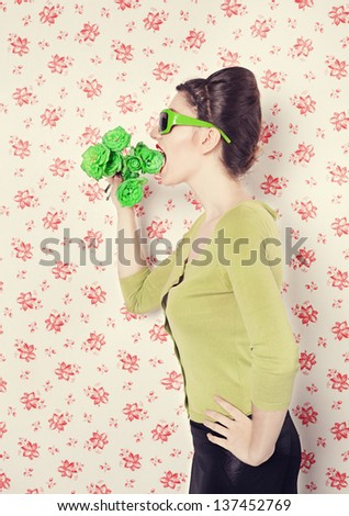 vegetarian lady eating green roses in front of retro wall background