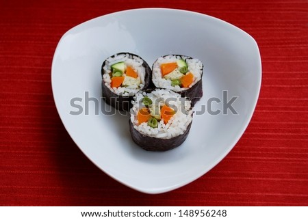 Vegetarian maki sushi rolls with rice, carrots, zucchini, green beans, tofu and nori seaweed in white dish on red background - stock photo