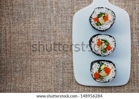 Vegetarian maki sushi rolls with rice, carrots, zucchini, green beans, tofu and nori seaweed in white dish on natural background, free space for text - stock photo