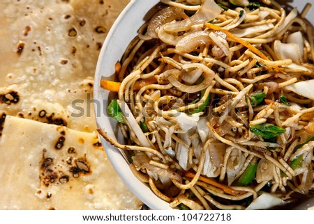 Vegetarian noodles and butter naan on the table in restaurant in Varkala, Kerala, India - stock photo