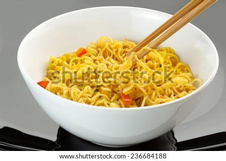 vegetarian noodles and chopsticks on black background - stock photo