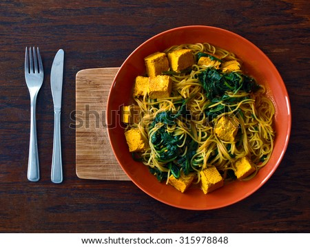 Vegetarian or vegan Indian food with noodles, spinach and tofu  - stock photo