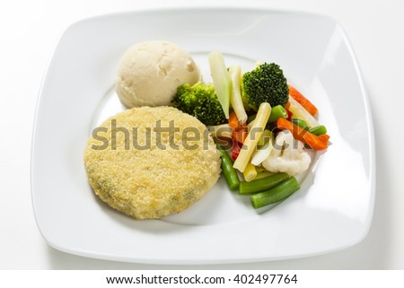 Vegetarian pattie with vegetables on a white plate - stock photo