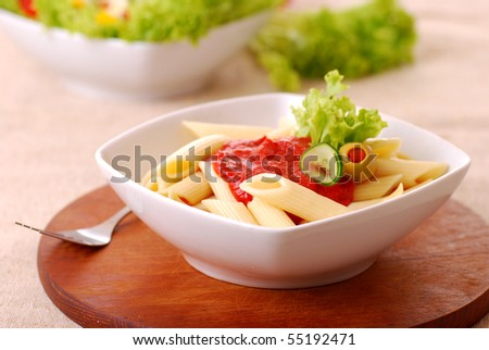 Vegetarian penne on a wooden plate closeup - stock photo