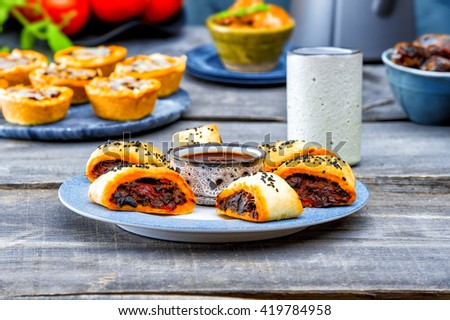 vegetarian pies with eggplant, red peppers, mushrooms with barbecue sauce. Picnic table with salty muffins, quiche, labneh,fresh tomatoes, mint on the old gray wooden table on stone texture background - stock photo