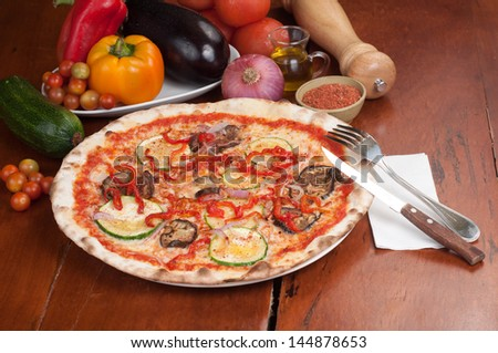 vegetarian pizza and ingredients on a brown board