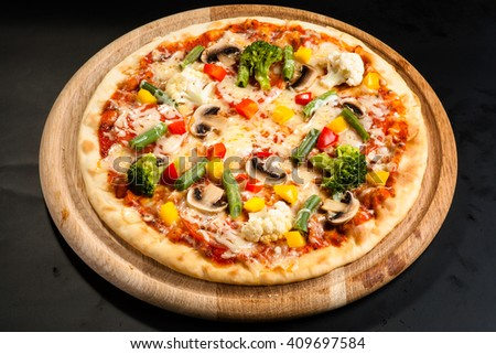 vegetarian pizza on a dark background with mushrooms, cheese and sweet pepper - stock photo