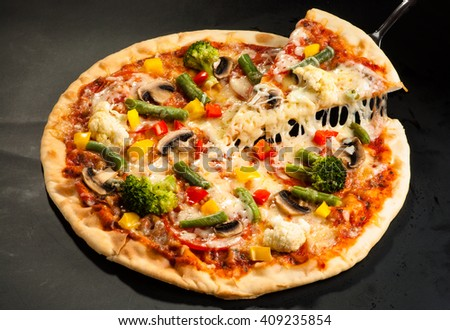 vegetarian pizza on a dark background with mushrooms, cheese and sweet pepper, cutting - stock photo