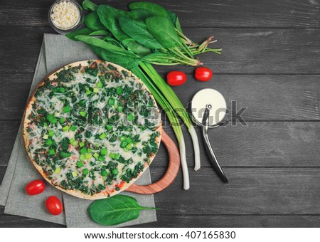 Vegetarian pizza with spinach leaves, mozzarella cheese, green onion, cherry tomatoes, knife on a black wooden background, top view, empty place for text, recipe - stock photo