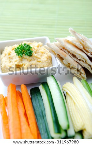 Vegetarian platter of raw carrots, corn, cucumber and celery sticks with chickpea dip and flatbread  - stock photo